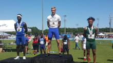 Charlotte's Devin Quinn stands on the podium with a gold medal around his neck after winning the 100-meter state championship Saturday.