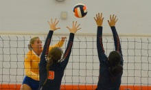 SUN PHOTO BY JENNIFER BRUNO          Charlotte's Emily Vaughn hits the ball through the hands of Lemon Bay players Ocie Flowers and Emily Schulte during the Tarpons game played against the Mantas.