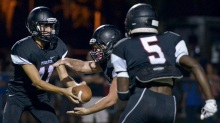 SUN PHOTO BY JENNIFER BRUNO          Port Charlotte's Paul Barnes hands off the ball to Brennan Norus during the game played against North Fort Myers on Friday evening.