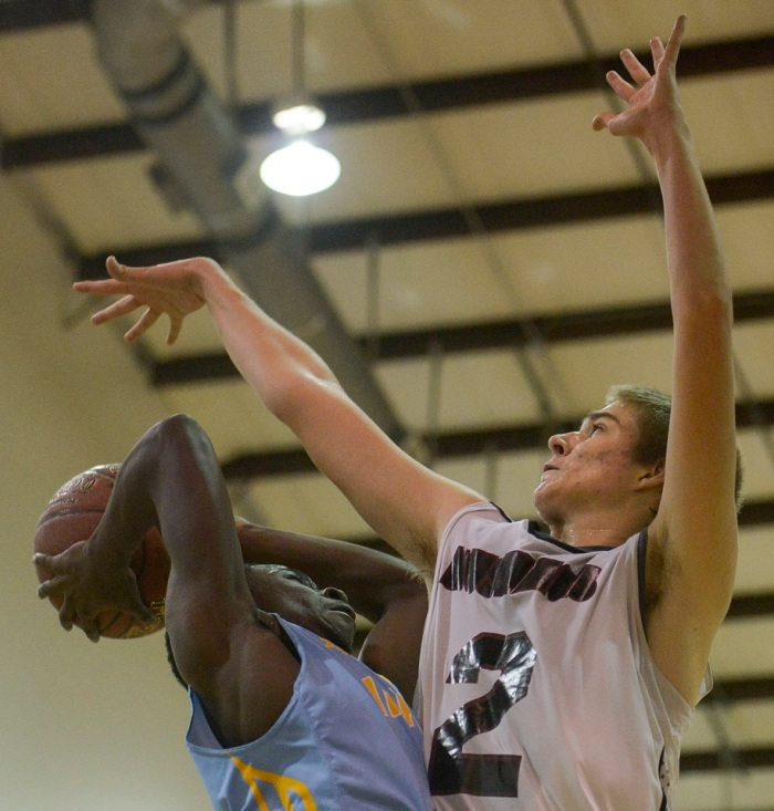 Imagine's Quadir Waters gets blocked by Community Christian's Blake Via on Tuesday. Sun photo by Jennifer Bruno