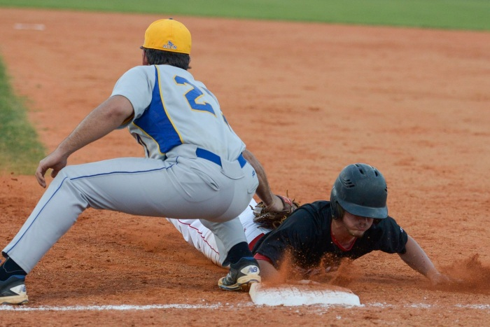 Charlotte's Robert Oettinger attempts to tag out Port Charlotte's Raven Jones as he slides back into first base. Sun photo by Jennifer Bruno