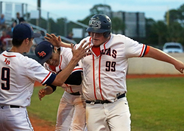 Lemon Bay's Zach Pellicciotti celebrates with teammates Warner Ricconnes and Brandon Gielow after scoring a run. Sun photo by Tim Kern