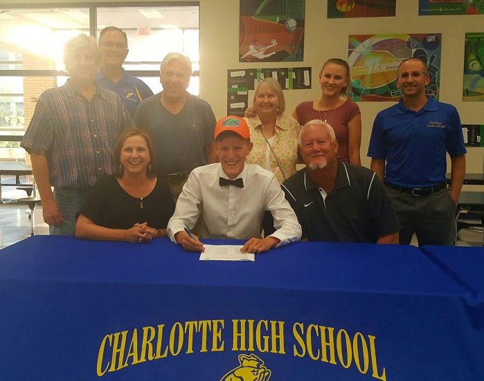 Charlotte's Marshall Dillon, center, signs his national letter of intent to run cross country and track for the University of Florida on Monday. Sun photo by Josh Vitale