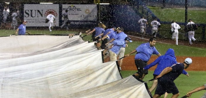 8/17  As the sky turned dark at the bottom of the sixth inning a stray bolt of lighting sent fans and players of both teams scrambling for cover as crews struggled to drape the field  (Sun Photo by Michele Haskell)