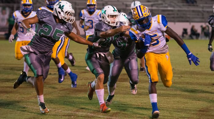 Charlotte's Savorion Warren runs the ball around Fort Myer's Pierre Chery(25), Benjamin Stobugh ( after an ), and Xavier Perez (7) after interception during Friday's game (Sun photo by Katherine Godina).