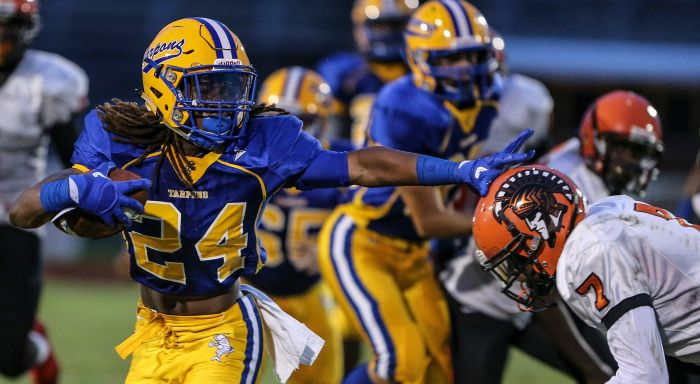 Charlotte running back D'Vonte Price stiff arms Lely defensive back Blazidy Duprat (7) during the first quarter Friday at Charlotte High School. (Sun Photo by Tom O'Neill)