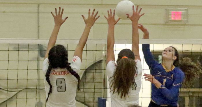 Charlotte's Shelby Beisner returns as Sarasota's Emily Sauceda (9) and Alex Montoya block during the 2nd set of Thursday night's game at Charlotte (Sun Photo by Michele Haskell)