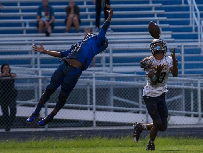 North Port's CK Poulos looks for the catch as Baker's Shomari Mason just misses tipping it during Friday's game at Ida Baker (Sun Photo by Katherine Godina)