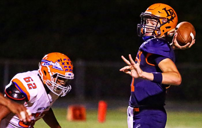Lemon Bay's Hayden Wolff stands in the pocket under intense pressure and delivers the pass (Sun Photo by Tim Kern).