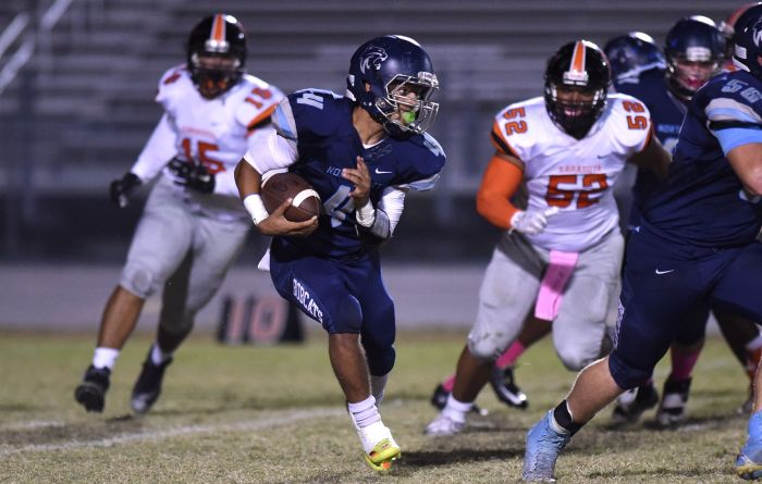 North Port's Javon Howell runs around Sarasota's Briyance Adams (52) on Friday night in North Port (Sun Photo by John Kersten).