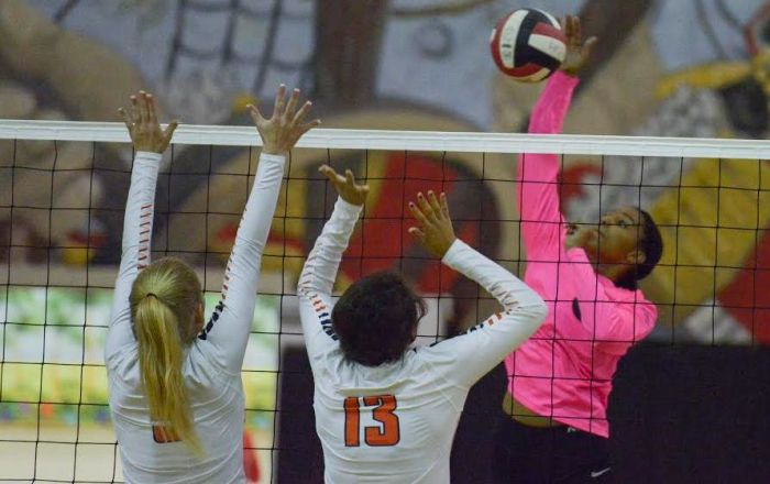 Port Charlotte's Kaelyn Griffiths hits the ball through the hands of Lemon Bay's Haylee Layne and Francesca Gallucci (Sun Photo by Jennifer Bruno).