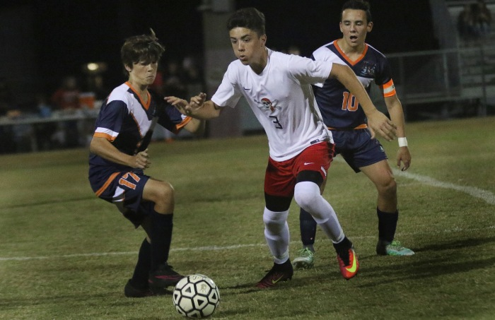 11/18/16 Port Charlotte's Nate Ruth drives the ball as Lemon Bay's Harley Rusher. left, and Matias Carbone move to defend ,during the 1st half of Friday night's game at Port Charlotte.