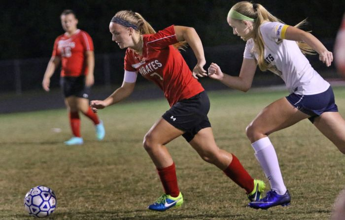 Port Charlotte's Doren Staley advances up the field   as North Port's Haley Royer moves to defend, during Thursday night's game in North Port (Sun Photo by Michele Haskell).