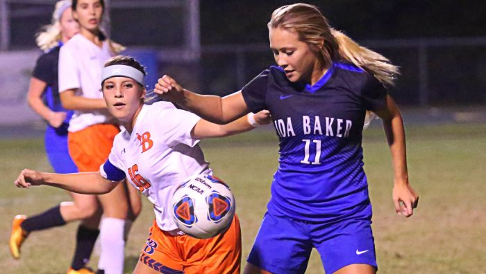 Lemon Bay High School's Stephanie Tieu works to get a play on the ball against Ida Baker's Hannah Lagmiri (Sun Photo by Tim Kern).