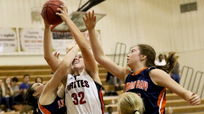 Port Charlotte's Celia Baermann battles for a rebound with Lemon Bay's Dominique Mamalis. left. and Abby Turner, during the 3rd quarter of Friday night's game at Port Charlotte (Sun Photo by Michele Haskell).