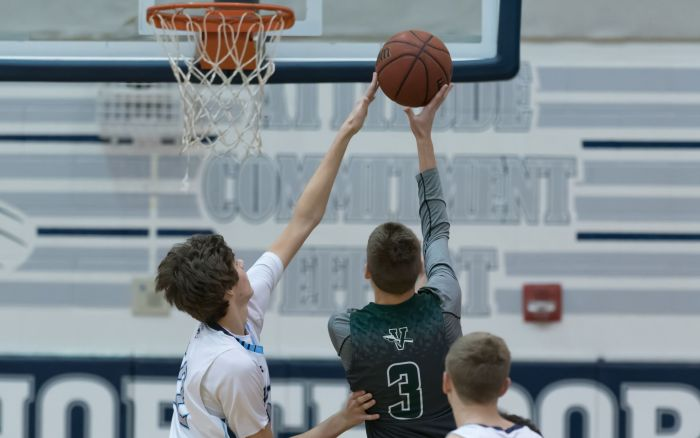North Port's Ben Via blocks the shot of Venice's Trent Holloway on Wednesday night in North Port (Sun Photo by John Kersten).