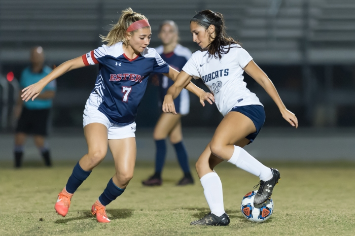 North Port's AD Trouche tries to get by Estero's Haley DeSanto on Thursday night during a FHSAA Regional Quarterfinal matchup in North Port (Sun Photo by John Kersten).