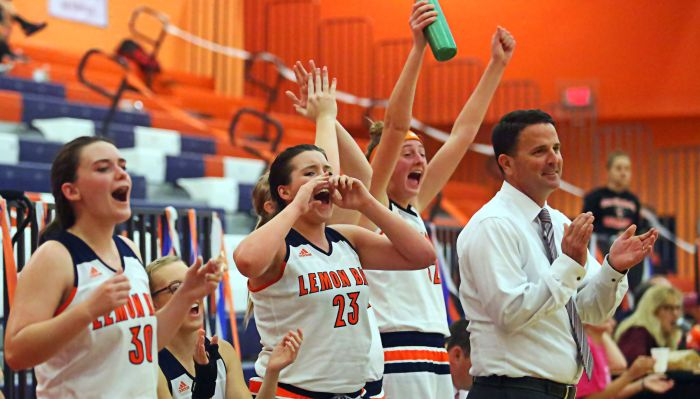 Lemon Bay High School's seniors celebrate a blow out win on Senior Night over North Fort Myers. Ryan Carley, Dominique Mamalis, Kelsey Hansen, and head coach Mike Young are all smiles as they cheer on their teammates late in the fourth quarter (Sun Photo by Tim Kern)