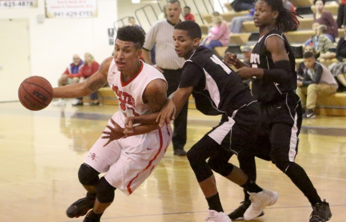 Port Charlotte's Sean Price drives up the court as DeSoto County's Donovan Evans defends, during Monday night's game at Port Charlotte (Sun Photo by Michele Haskell).