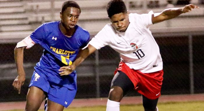 Port Charlotte's Justin Ross,right, drives up the field as Charlotte's Donal Rateau moves to defend during Thursday night's game (Sun Photo by Michele Haskell).