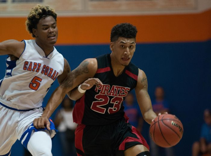 Port Charlotte's Sean Price drives around Cape Coral's Cam'ron Blissett during Tuesday's game (Sun Photo by Kat Godina).