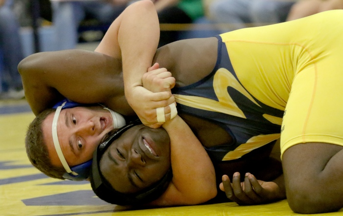 Charlotte's Dalton Mills holds his opponent Dinel Chery of Naples on the mat during Saturday's match (Sun Photo by Michele Haskell).